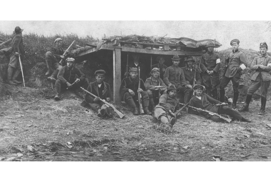 Kilkunastu powstańców na tle umocnień wojskowych. Kilku mężczyzn stoi, kilku siedzi, kilku leży. W rękach trzymają broń. Zdjęcie czarno-białe z roku 1921.