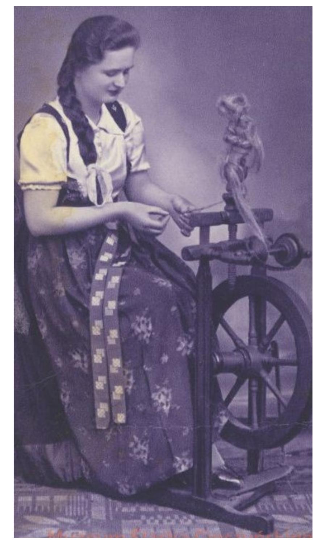 Czarno-biała fotografia przedstawiająca kobietę przędzącą.