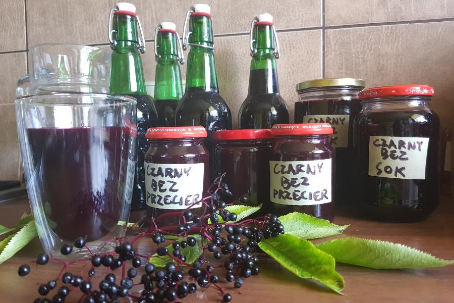 Butelki i słoiki z przetworami z bzu czarnego. Całość stoi na kuchennym stole. Na pierwszym planie owoce bzu czarnego